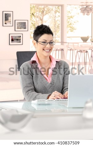Happy young casual caucasian businesswoman working at home on laptop computer, wearing glasses, sitting at desk, looking at screen, typing, doing business. Smiling. - stock photo