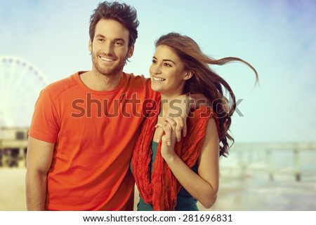 Happy young casual caucasian couple walking at seascape holiday outdoor beach. Holding hands, smiling, copyspace.