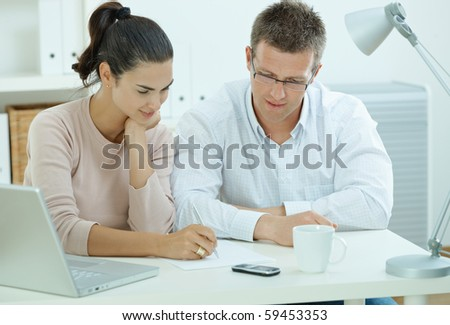 Happy young casual couple sitting  at desk working together at home office, smiling. - stock photo