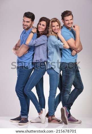 happy young casual group of people standing together and smile on grey studio background - stock photo
