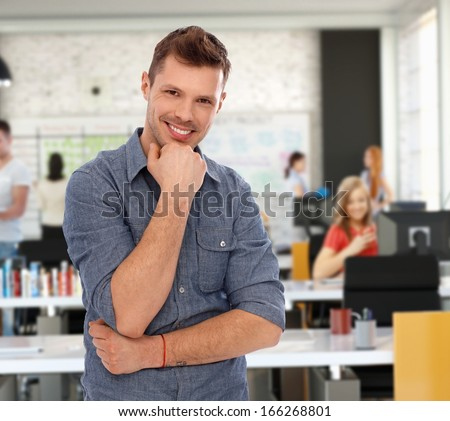 Happy young casual man at trendy youthful office.