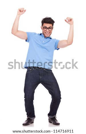 happy young casual man celebrating, cheering with both his arms in the air,  isolated over a white background - stock photo