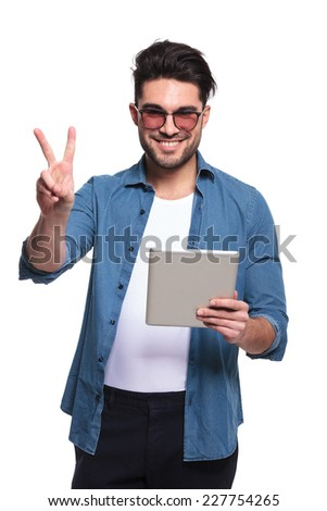 Happy young casual man holding a computer tablet while showing the victory sign, isolated.