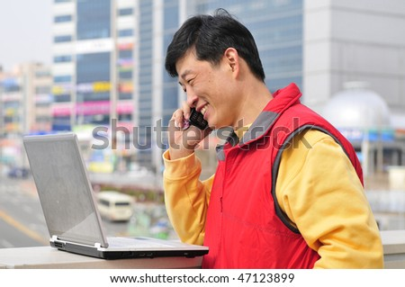 Happy young casual man outdoor with laptop