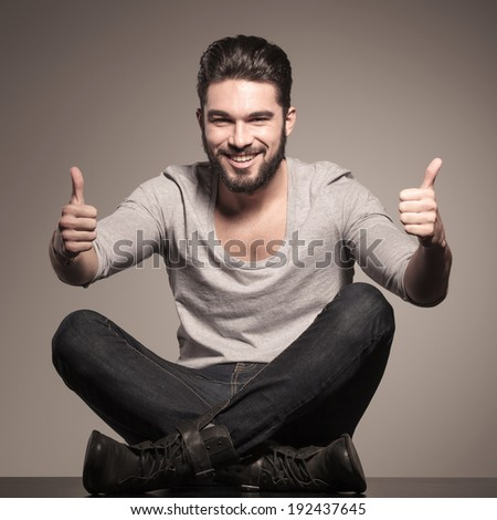 happy young casual man sits and make the ok thumbs up hand sign - stock photo