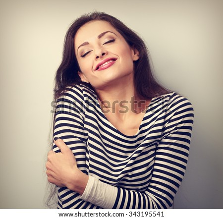 Happy young casual woman hugging herself with natural emotional enjoying face. Love concept by yourself. Vintage closeup portrait