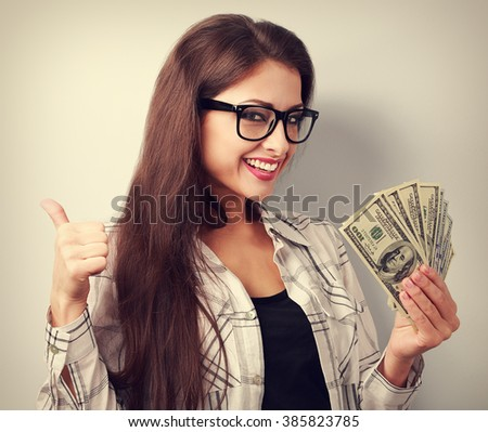 Happy young casual woman in glasses holding dollars and showing thumb up sign with toothy smiling. Toned portrait - stock photo