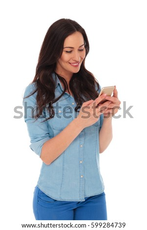 happy young casual woman reading messages on her phone isolated on white background
