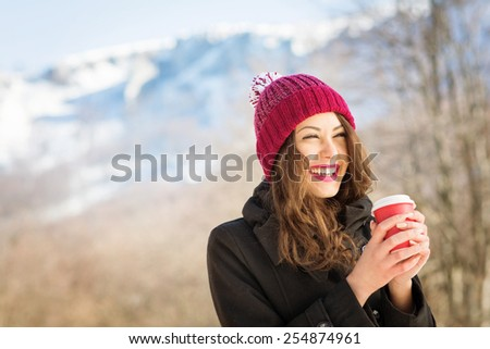 Happy young Caucasian brunette woman with red lips and red beanie hat with takeaway coffee outdoors in winter. Snowy mountain blurred in the background. Retouched, natural light, copy space. - stock photo