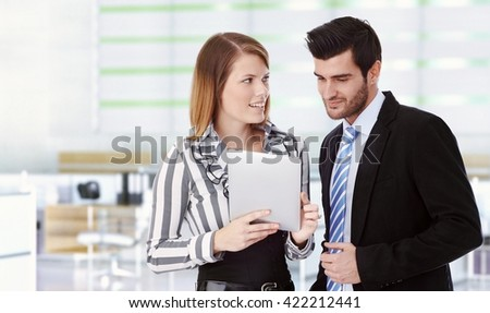 Happy young caucasian business people with tablet computer at office. Attractive woman and handsome man. Smiling, standing, wearing suit, looking at screen. Copyspace.