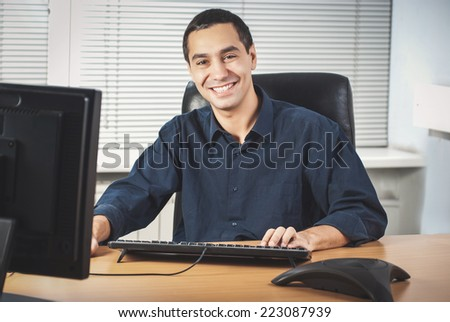 Happy young caucasian businessman in his office - stock photo