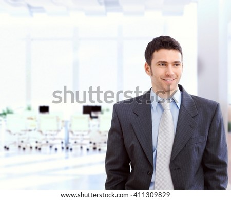 Happy young caucasian businessman in suit and tie at bright office. Standing, smiling, copyspace. - stock photo