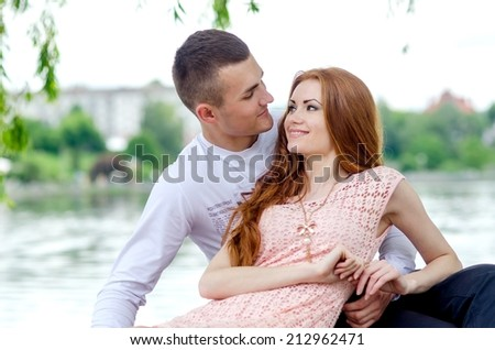 Happy young caucasian couple at the park - stock photo