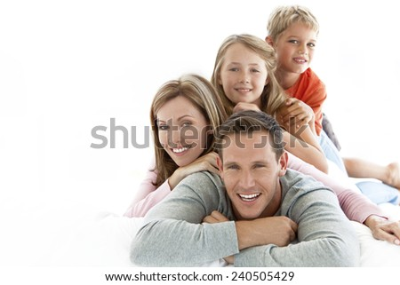 Happy young Caucasian family making a human pyramid - stock photo