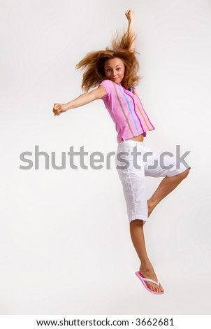 Happy young caucasian female jumping into the air - stock photo