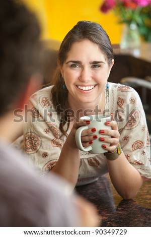 Happy young Caucasian lady with mug and friend - stock photo