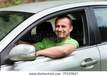Happy young caucasian man at the wheel of his new car - stock photo