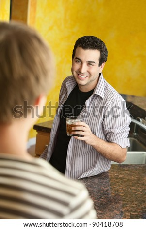 Happy young Caucasian man enjoys a drink with friend in kitchen