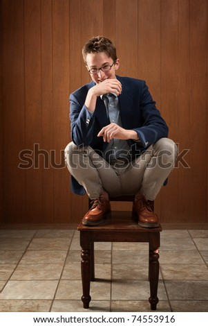 Happy young Caucasian man on a chair
