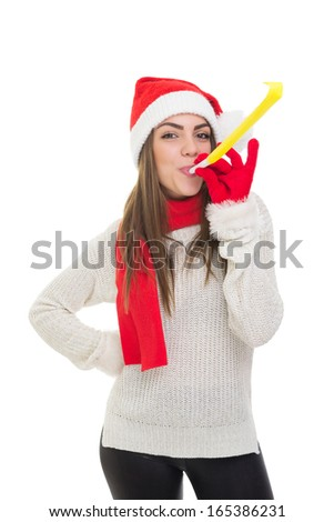 Happy young Caucasian pretty brunette girl wearing Santa Claus beanie hat and red gloves and scarf blowing a yellow party blower whistle posing with hand on hip isolated on white background. - stock photo