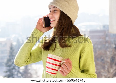 Happy young Caucasian teenage woman talking on the phone laughing holding  cup smiling. Outdoors winter portrait of beautiful teenage girl speaking on the phone.