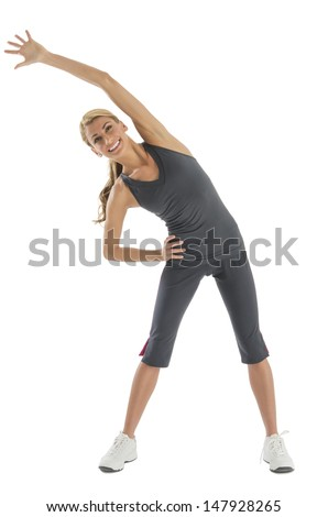 Happy young Caucasian woman in fitness clothing doing stretching exercise against white background - stock photo