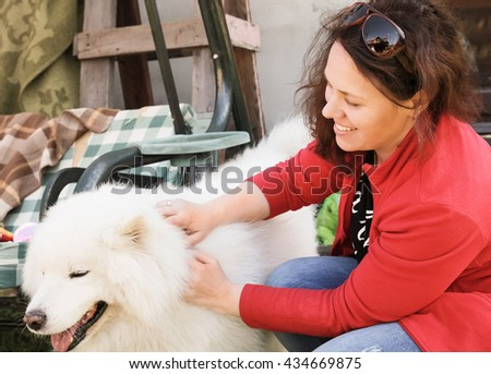 Happy young Caucasian woman with white fluffy Samoyed dog, outdoor portrait - stock photo
