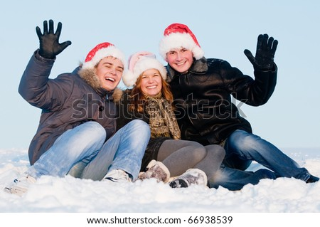 happy young cheerful people sitting in snow at winter outdoors - stock photo