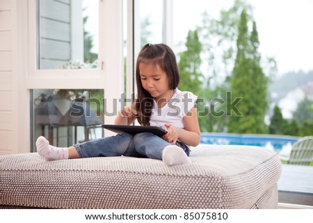 Happy young child playing with a digital tablet in an indoor setting - stock photo