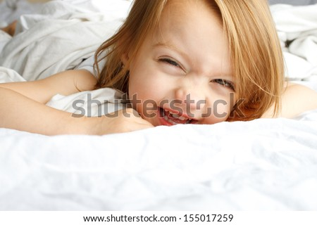 Happy young child smiling in white blankets - stock photo