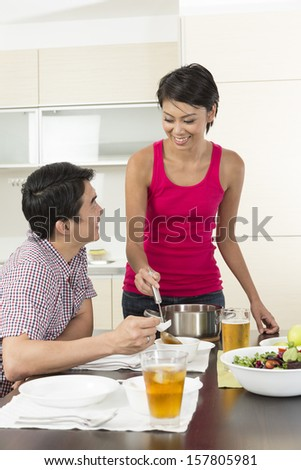 Happy young Chinese couple preparing to eating dinner at home in the kitchen - stock photo