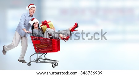 Happy young Christmas couple with shopping cart over blue background. - stock photo