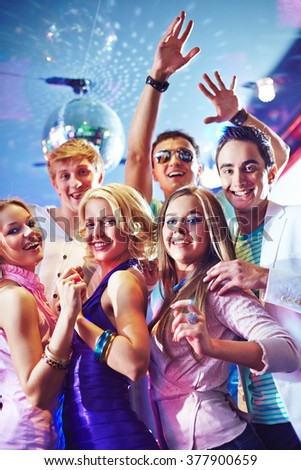 Happy young clubbers dancing at party - stock photo