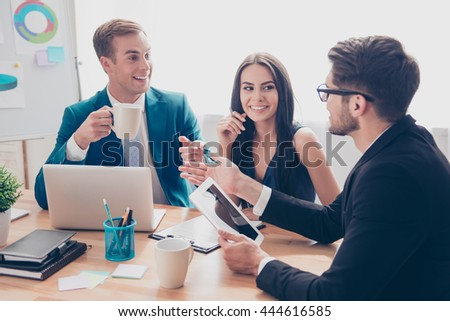 Happy young colleagues having coffee break and talking - stock photo