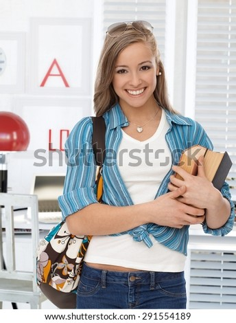 Happy young college student holding books, smiling, looking at camera. - stock photo