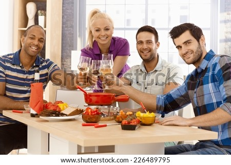 Happy young companionship clinking glasses around dinner table, smiling, looking at camera. - stock photo