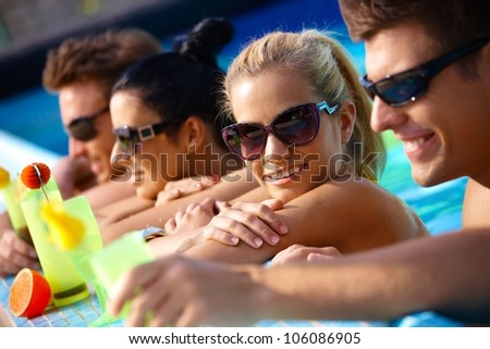 Happy young companionship in water, drinking cocktail, smiling. - stock photo