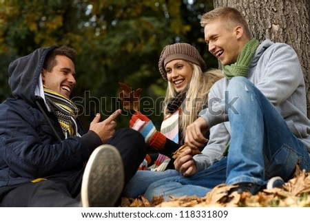 Happy young companionship sitting, talking in autumn park. - stock photo