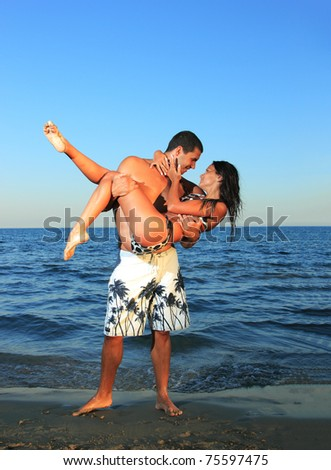 Happy young couple about to kiss at the beach - Man is carrying the girl - stock photo