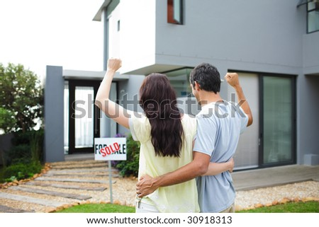 Happy young couple after buying house - stock photo