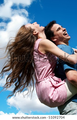 Happy young couple against the sky - stock photo