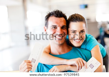 happy young couple at airport with boarding pass