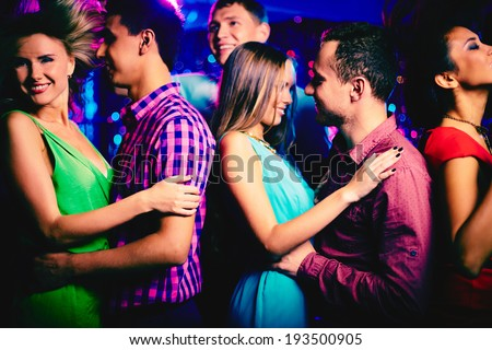 Happy young couple at disco surrounded by their dancing friends - stock photo