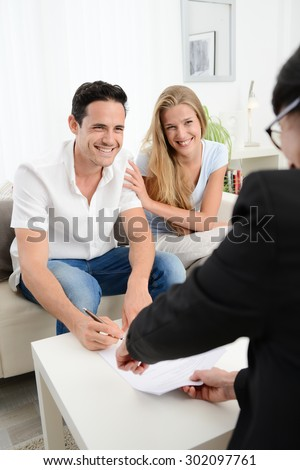 happy young couple at home in transaction signing contract with a business woman - stock photo