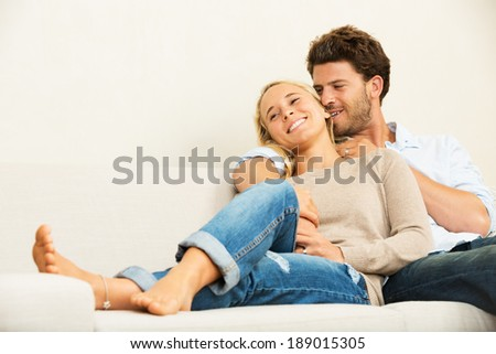 Happy young couple at home relaxing on the sofa - stock photo