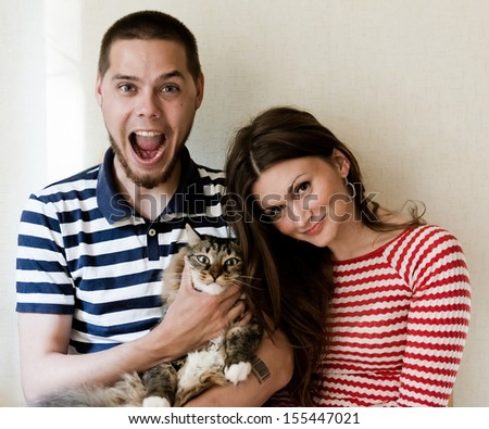 happy young couple at home with their cat  - stock photo