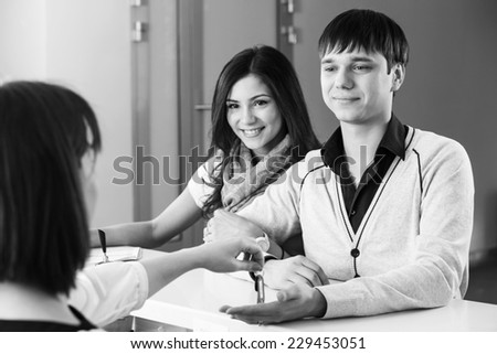 Happy young couple at hotel reception receiving the key of the room. - stock photo