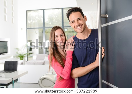 happy young couple at new house front door welcoming people  - stock photo