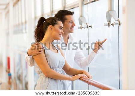 happy young couple at restaurant pointing outside - stock photo