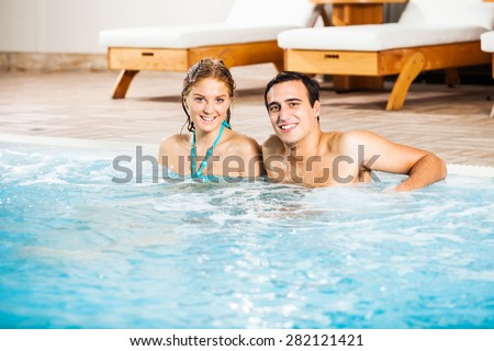 Happy young couple at swimming pool - stock photo